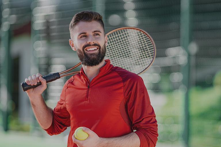 mężczyzna zrakietą tenisową wczerwonej koszuli